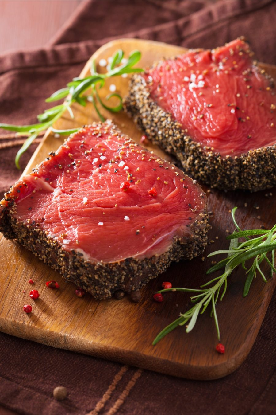 raw-beef-steak-with-spices-and-rosemary-on-wooden-PYKY6QV